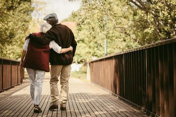 Obraz Senior couple in warm clothing walking together in park - fototapety do salonu