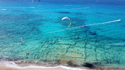 Aerial drone photo of famous for watersports like kitesurfing sandy turquoise beach of Agios Ioannis with old abandoned wimdills and lovely clouds, Lefkada island, Ionian, Greece