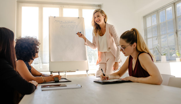 Woman giving presentation on budget to colleagues