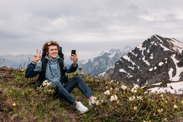 young positive hiker with victory gesture is taking a selfie. amazing breathtaking scinery on the background