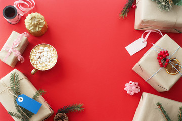 Christmas gifts among the decorations next to a cup of cocoa with marshmallows on a red background . Top view, flat lay, copy space