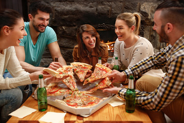 Group of young people taking pieces of big family pizza