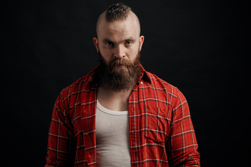 Portrait of serious young bearded man standing against black background