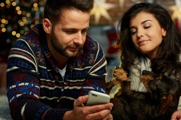 Christmas couple with phone at home in Winter