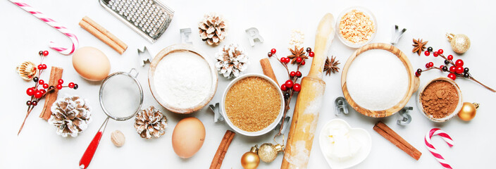 Christmas or New Year composition with ingredients for baking festive cookies, with golden snowflakes, Christmas balls, pine cones on white background, banner, top view