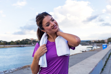 Portrait of young woman runner stretching neck