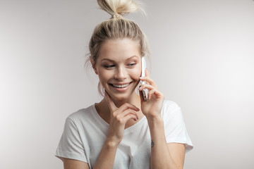 Pretty, charming, caucasian girl in white t-shirt talking on smart phone with her lover, feeling happiness and joy, dreaming about next date, isolated on white background,
