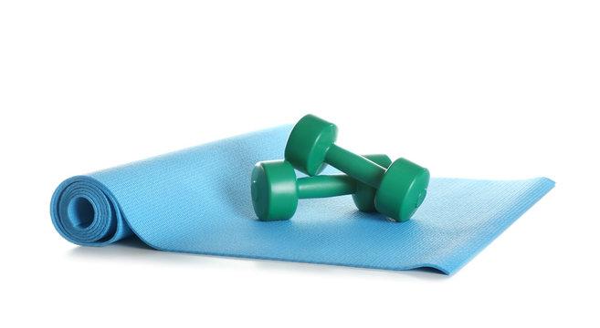 Yoga mat with dumbbells on white background