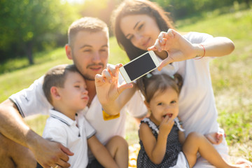 Cheerful family doing selfie outdoors