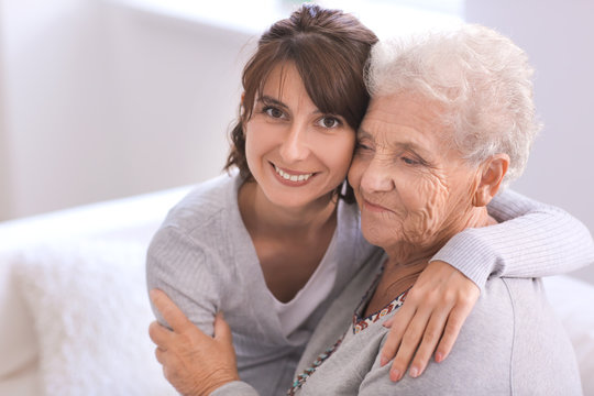 Happy elderly woman with her daughter at home