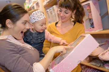 happy mom and daughter checking doll at the toy store