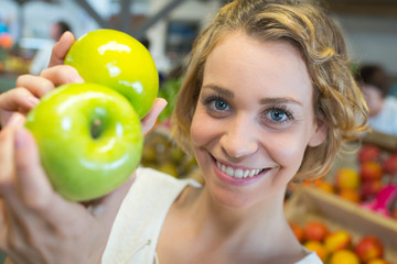 girl holding green apples