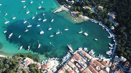 Aerial drone bird's eye view photo of iconic small port and fishing village of Lakka with traditional Ionian architecture and sail boats docked, Paxos island, Ionian, Greece