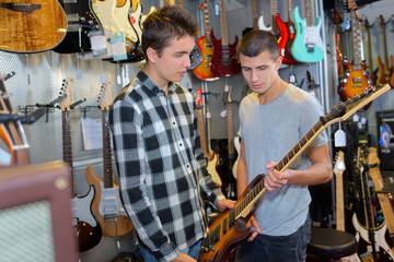 Young man holding guitar in store