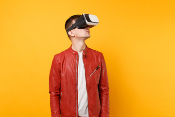 Portrait vogue cute young man in red leather jacket t-shirt looking up in headset standing isolated on bright trending yellow background. People sincere emotions lifestyle concept. Advertising area.