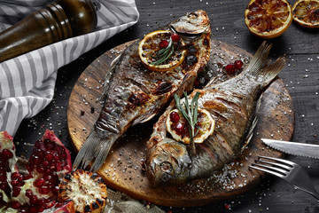 Grilled carp with lemon on wooden board, horizontal view from above close-up