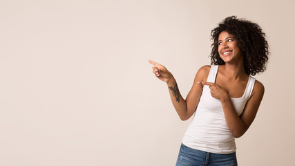 Happy african-american woman pointing away at copy space
