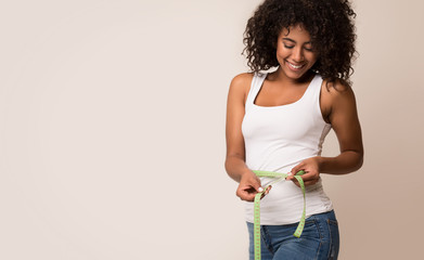 African-american woman measuring waist and looking on tape