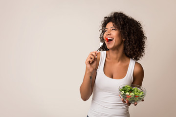 Excited lady eating healthy salad over light background