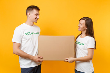 Colleagues couple in white t-shirt with written inscription green volunteer hold cardboard box donations isolated on yellow background. Voluntary free assistance help, charity grace teamwork concept.