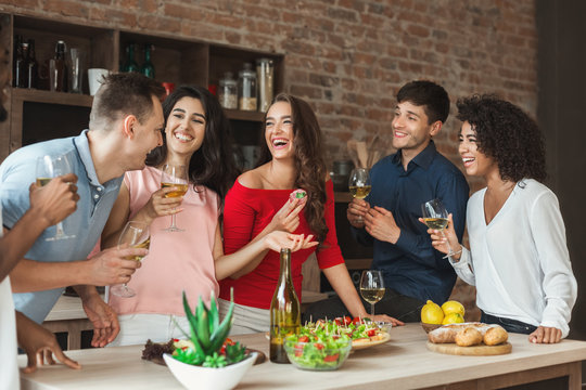 Multiracial friends enjoying small party at home