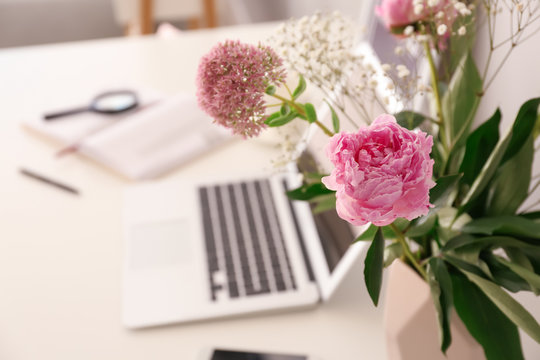 Vase with beautiful pink flowers and laptop on table