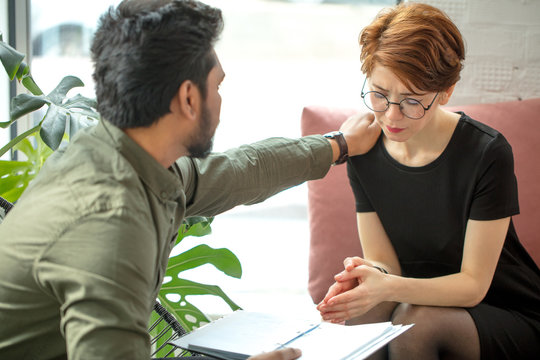 male psychiatrist touching on stress patient woman shoulder to cheer up him from sadness