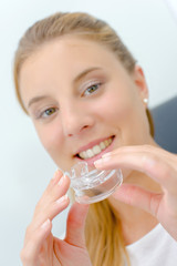 Woman about to use a mouth guard whilst at the dentist