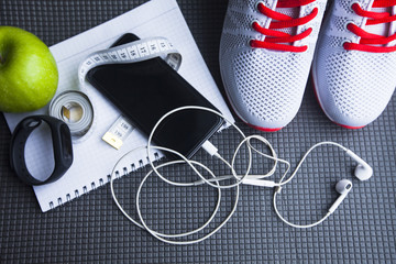 Time for diet slimming weight loss concept. Sport fitness, apple, sneakers, bottle of water and yellow weights on grey rubber background. Vintage retro instagram filter