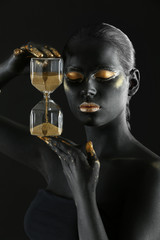 Beautiful woman with black and golden paint on her body holding hourglass against dark background