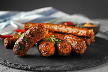Tasty grilled sausages on slate plate