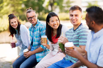 people, friendship and international concept - group of happy friends drinking coffee and juice talking in city