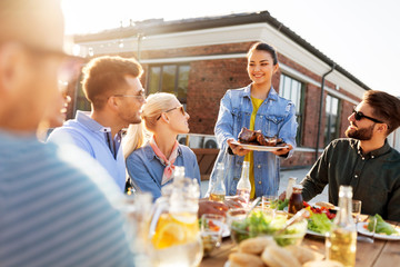 leisure and people concept - happy party host offering meat to his friends at barbecue party on rooftop in summer