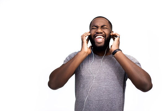 Young handsome black man, listening to music on headphones, smiling face expression, positive mood, happy emotion, isolated on white background, african american youth, hipster, technical adversise