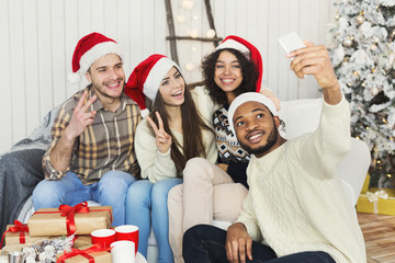 Happy young friends taking Cristmas selfie photo