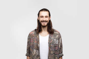 Glad positive male hippie happy to belong to this youth subculture, has specific appearance, has broad smile on face, isolated on white background. Hippy man, hipster lifestyle emotions concept