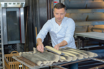 Baker putting baguettes on tray to cook