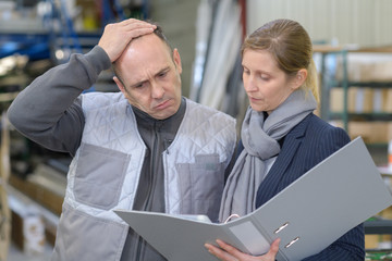 man frowning while looking at folder held by woman