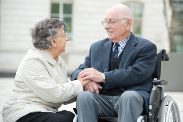 couple in wheelchair talking together visiting the city