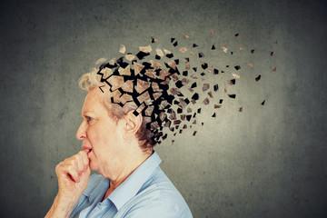 Senior woman losing parts of head feeling confused as symbol of decreased mind function. Wall mural