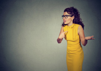 Angry woman pointing at herself in misunderstanding