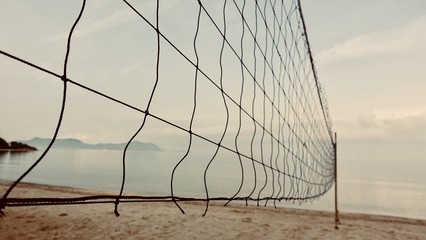 A beach volleyball net on a sunny day, on an empty beach