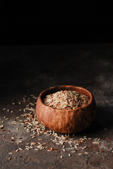 Brown, red and black rice mix which is strewing into a clay bowl on a grange concrete dark background. Dark and moody image. Close up. Copy space