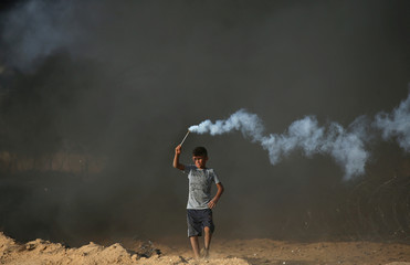 Palestinian boy holds a tear gas canister fired by Israeli troops during a protest at the Israel-Gaza border fence in the southern Gaza Strip