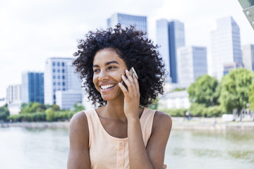 Germany, Frankfurt, portrait of smiling young woman with curly hair on the phone