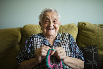 Portrait of smiling senior woman crocheting at home