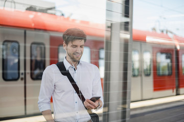 Smiling businessman on station platform with earphones and cell phone