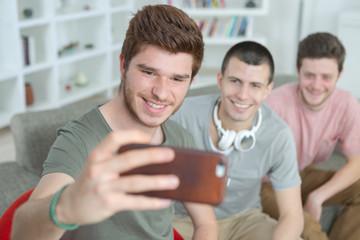 three guys doing selfie in home interior