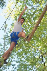Man on adventure course through trees