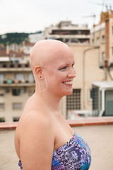 Bald woman in top standing on rooftop
